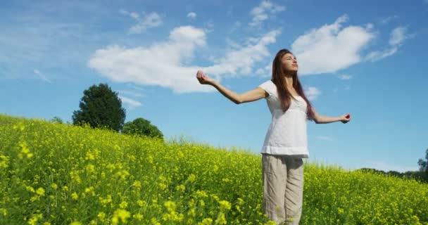 video z šťastná žena, dýchat čerstvý vzduch a stojící na zelené trávě louku a točí kolem
