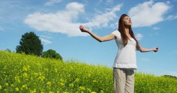 videó a boldog nő, friss levegőt lélegzik, és állandó zöld fű réten körül forog