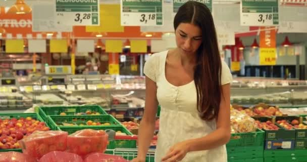 A beautiful young girl (woman) at the grocery store, in a white tank top, supermarket, chooses alcoholic drinks products, with a cart. Concept: buy products, large purchases, market, store, products.