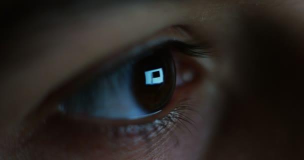 Zavřete video natočené lidského hnědé tmavé oko, reflexe na obrazovku monitoru v oku