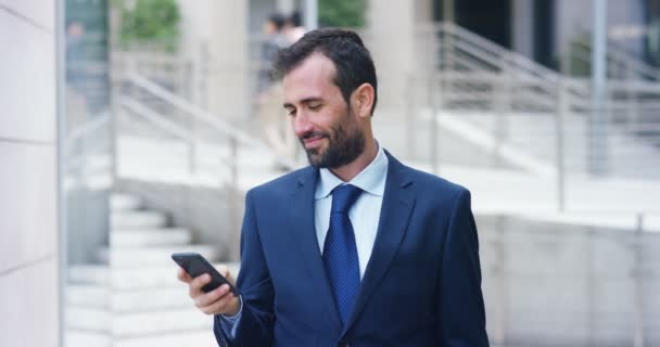 video of Caucasian businessman in suit and neck tie browsing mobile phone, reading message and laughing