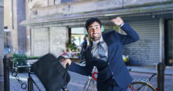 Zeitlupenvideo eines glücklichen kaukasischen Geschäftsmannes, der im Freien tanzt und Erfolge feiert und Koffer in der Hand hält, Straße mit Fahrrädern im Hintergrund