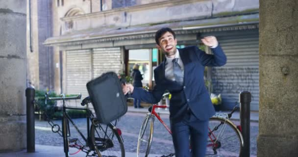 video of happy businessman dancing and celebrating success outdoors and holding case bag, street with bicycles on background