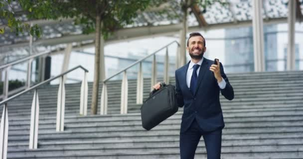 video of happy Caucasian businessman looking at mobile and celebrating  success outdoors and holding case bag while standing on stairs