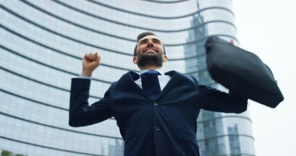 zpomalené video šťastný kavkazských podnikatel v obleku a krku tie slaví úspěch venku a drží taška při pózování v moderní skleněné kancelářské budovy