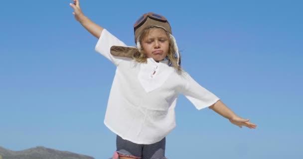 boldog baba játszik ég kék ég, hogy egy pilóta karokkal nyitott és mosolygós, hogy álmai játszik. koncepció az élet és az utazás a család és a boldogság