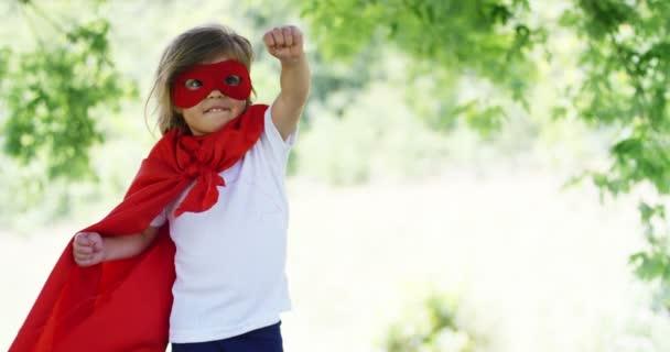 in una bella e felice giornata di sole, una ragazza poco vestita come un super eroe fa espressioni e cercare di volare nella natura variopinta, il bambino ride felice. concetto di felicità, amore e natura.