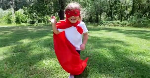 v krásné a šťastné slunečný den, malá dívka oblečená jako super hrdina dělá výrazy a snaží se létat v barevné přírody, směje se šťastné dítě. pojem štěstí, láska a příroda.