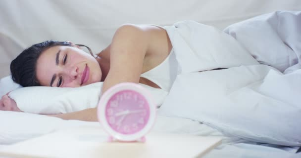 Egy gyönyörű fiatal lány gyenge fel a meleg ágyban, az ébresztő kikapcsolása egy egyszerű munkanap borított puha meleg fehér takaró, fehér alapon.