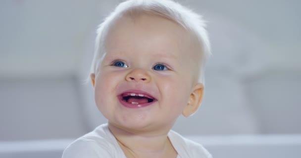 Dítě, chlapec s velké modré oči a světlé vlasy, sedí a usměje se na sněhobílé deku, se dívá na její matku, na bílém pozadí. Koncepce: děti, děti, dítě, děti, nové generace.