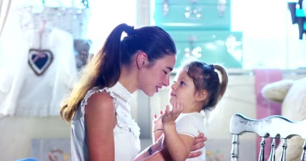 Doma, v ložnici matka a dcera hrát a dát na líčení, česání vlasy dohromady. Matka a dcera usmívala se, když se snaží beauty triky. Koncepce: krása, Rodina, zábava, vzpomínky.