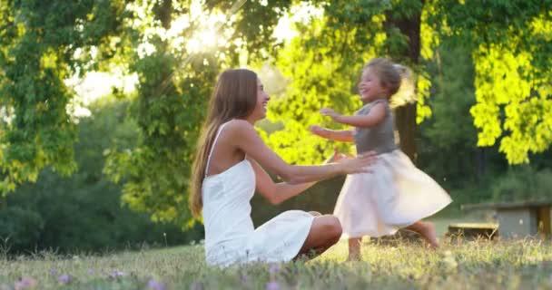 ekologie, mladá matka s její rozkošný dva let stará dívka hraje venku s láskou. koncepce rodinné lásky k přírodě. šťastné děti s láskou rodiče. koncept zelené a udržitelnost.