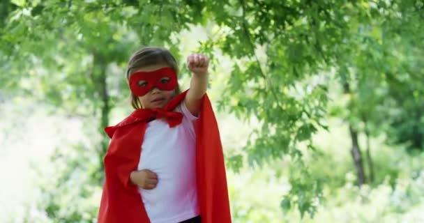 egy szép és boldog napsütéses napon, egy kis lány öltözött, mint egy szuper hős teszi kifejezések, és próbálja meg repülni, a színes a természetben, a gyermek boldog nevet. fogalom a boldogság, a szeretet és a természet.