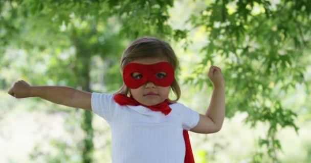 in una bella e felice giornata di sole, una ragazza poco vestita come un super eroe fa espressioni e cercare di volare nella natura variopinta, il bambino ride felice. concetto di felicità, amore e natura