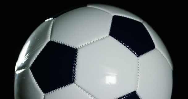 video z předení fotbalové míče na černém pozadí