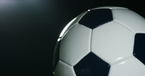 video of spinning football balls on black background, studio shot