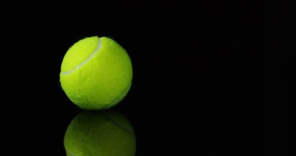 Studio záběr, točí video ze zelené tenisové míčky na černém pozadí