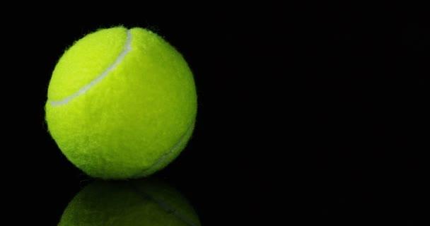 točí videa zelené tenisové míčky na černém pozadí