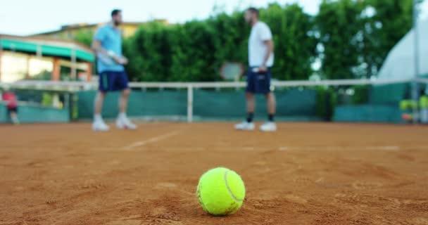 Zpomalený pohyb okouzlující mladý tenista provádí s jeho nejlepší snímky a učit v profesionálním prostředí v červené půdě v Krásný slunečný den, koncept vášně a výzvy