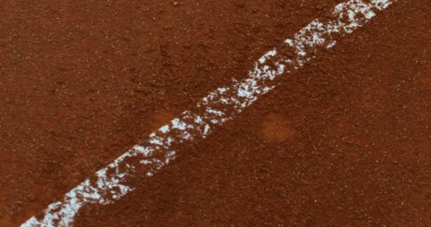 Zpomalený pohyb profesionální tenisovou raketu a hřiště v pozadí červené půdy s tenisový hráč rozostření