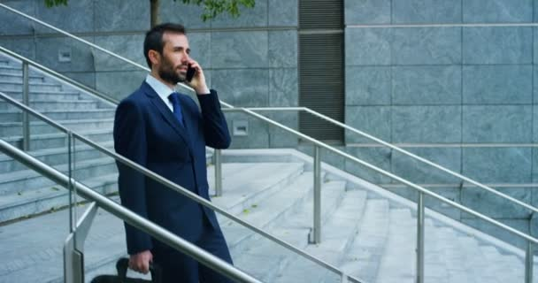 A businessman answering the phone, send messages and smiles for the beautiful job news and in the background you see a people. Concept: technology, telephony, business trips, business, wall street