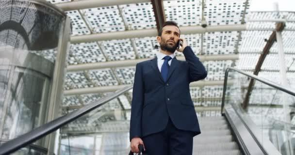 ein Geschäftsmann am Telefon, sendet Nachrichten und lächelt für die schönen Jobnachrichten und im Hintergrund sieht man ein Volk. Konzept: Technologie, Telefonie, Geschäftsreisen, Business, Wall Street