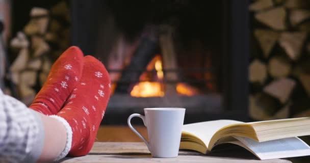 kalter Herbst oder Winterabend. Menschen, die sich mit Decken und Tee am Feuer ausruhen. Nahaufnahme von Füßen in Wollsocken. Gemütliche Szene.