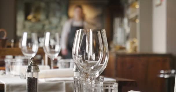 Číšník nastaví tabulky v restauraci, než zákazníci dorazí a používá jemné příbory a skleničky. Koncept: stravování, design, romantické večeře