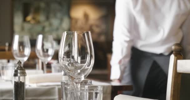 A waiter sets the table in a restaurant before customers arrive, and uses fine cutlery and glasses. Concept of: catering, design, romantic dinners
