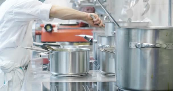 Kuchař, v profesionální kuchyni, vaří jídlo pro své zákazníky Restaurace v ocelové hrnce. Koncept: jídlo, kuchyně, kuchař, gurmán