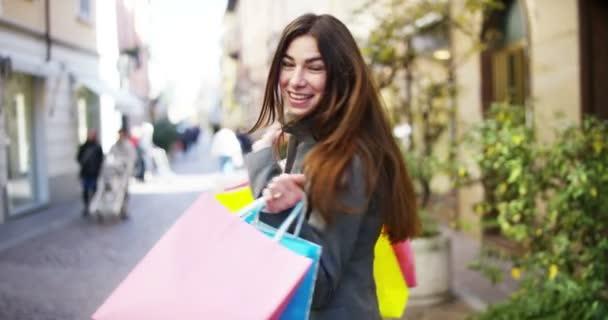 video z Černovlásky nakupující žena, která nosí barevné nákupní tašky