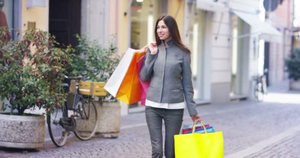 videó a shopaholic nő séta és a színes bevásárló táskák utcában