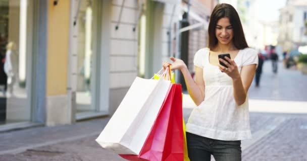 video z nakupující žena držící barevné tašky a prohlížení mobilních telefonů