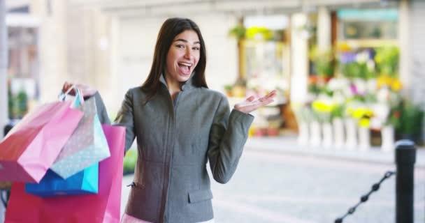 videó vicces boldog vásárló nő gazdaság színes bevásárló táskák