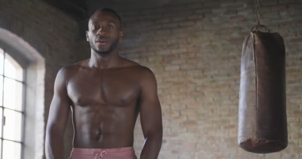 slow motion video of shirtless muscular african man looking at camera and standing at punching bag