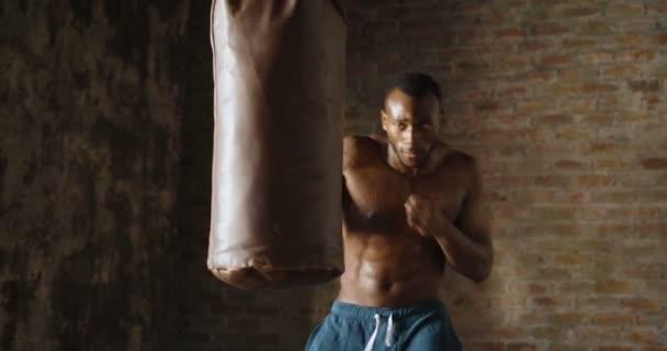 slow motion video of handsome shirtless muscular boxer african man punching bag