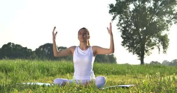 videó a szabadban, zöld fű rét, meditáció póz jóga nő