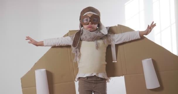 malý chlapec, oblečený jako pilotní hrát s ručně vyráběné krabice letadlo, slow motion videa