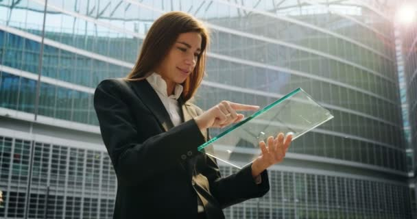 slow motion video of businesswoman using and browsing transparent digital tablet and standing at office glass building