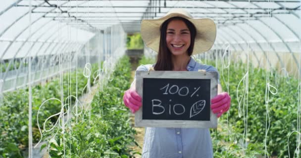 slow motion video of farmer woman in green house wearing hat, rubber gloves and showing chalk board, 100 percent bio
