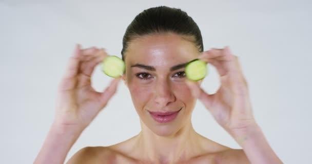 Portré, fiatal nő arcpakolás és uborka kezelés az arcán van kikapcsolódni egy wellness-központ. Bőrápolás, kozmetikumok, kozmetika, arckezelés, arcmasszázs, jólét fogalmának