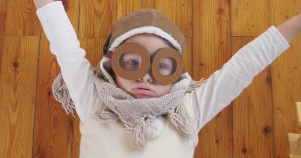 video hravá roztomilá holčička oblečený jako pilotní ležící na dřevěné podlaze s letadlo hračka