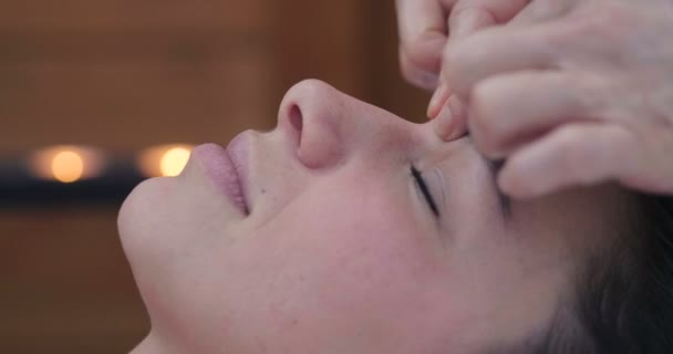 Nahaufnahme des Gesichts einer schönen Frau, die sich in einem Wellness-Center von einer erfahrenen Masseurin massieren lässt. Konzept von: Wellness, Entspannung, Erholung, Massage