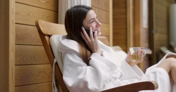 eine schöne Frau in einem Wellnessbereich, gekleidet in einen weißen Bademantel, trinkt einen heißen Kräutertee und benutzt ihr Handy, um Nachrichten zu senden. Konzept von: Technologie, Entspannung, Wellness, Netzwerk, Soziales.