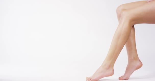 Mladá žena s dokonalým tělem použití osvěžující krém/tělové mléko na její nohy ion s bílým pozadím. Pojem depilace, hladká kůže, péče o pleť, kosmetika, wellness centrum, zdravého životního stylu