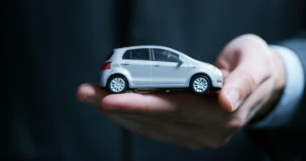 Egy ember öltözött egy öltöny és a nyakkendő, azt mutatja, egy kis kocsi. Koncepció: gépjármű-biztosítás, mechanikus, lízing, vásárlási új és használt autók és a nyilvános garázs.