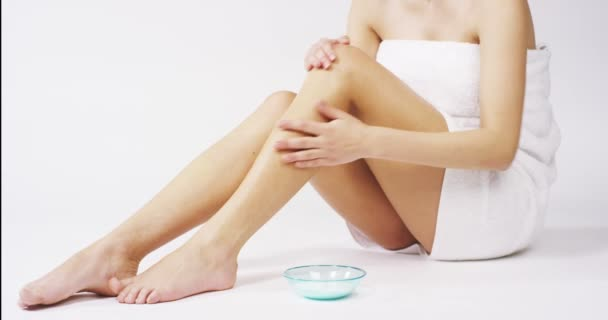 The young woman with perfect body applying refreshing cream/body lotion on her legs ion a white background. Concept of depilation, smooth skin, skincare, cosmetics, wellness center, healthy lifestyle