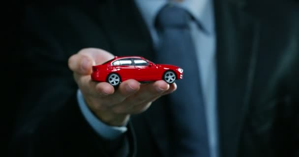 A man dressed in a suit and tie, shows a small auto. Concept: car insurance, mechanical, leasing, purchase new and used cars and public garages.
