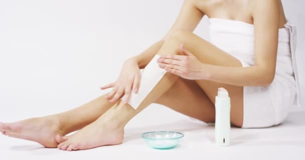 The young woman with perfect body doing depilation or her legs with waxing isolated on a white background. Concept of depilation, smooth skin, skincare, cosmetics, wellness center, healthy lifestyle