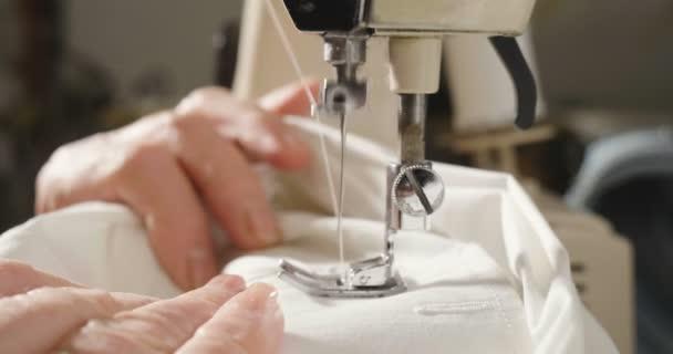 Super zpomalené profesionální šicího stroje, šití s bílým drátem italský couture tkaniny, švadlena šije vysoce módní oblečení. pojem průmyslu, tradice, móda